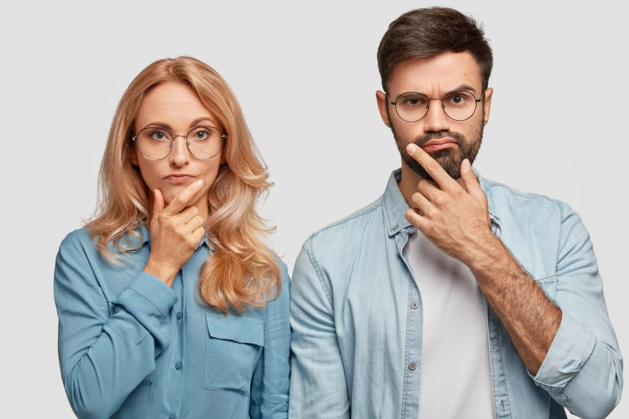 Thoughtful man and woman colleagues hold chins and being concentrated on solving problem look directly