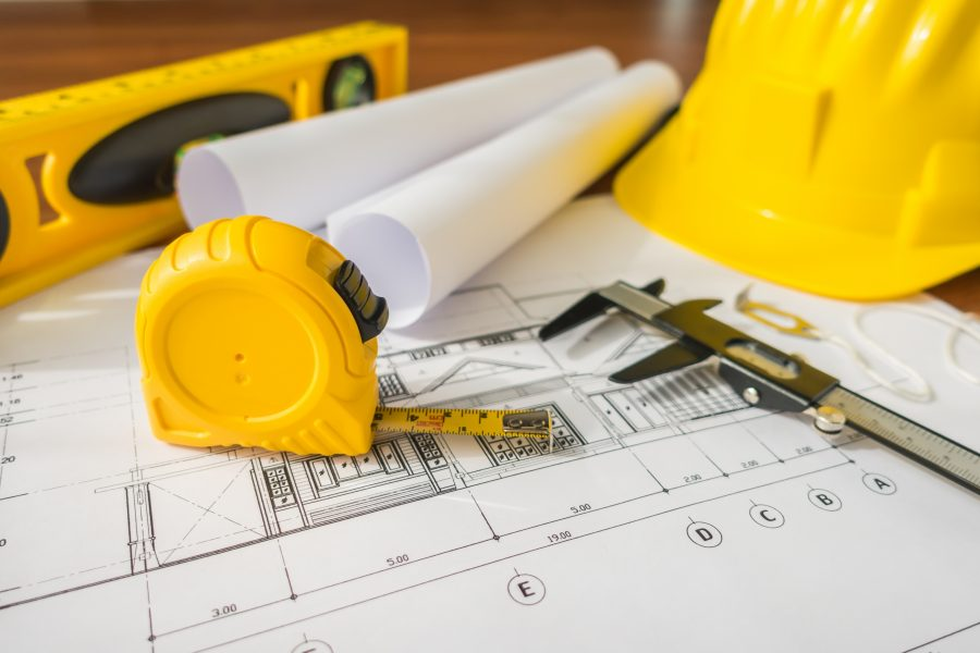 Construction plans with yellow helmet drawing tools bluep