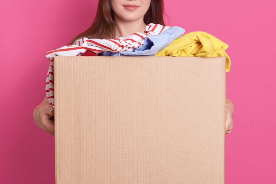 Indoor portrait faceless girl standing with cardboard box hands holding carton box full fashionable clothes isolated rosy wall donation charity volunteering concept